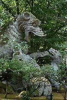 Bomarzo, Viterbo - Parco dei Mostri o Sacro Bosco, complesso monumentale realizzato nel 1547con grandi sculture di figure mitologiche del genere grotesque. Drago con leoni<br /> Bomarzo, Viterbo - Monster Park or Sacro Bosco, a monumental complex built in 1547 with large sculptures of mythological figures such grotesque. Dragon with lions