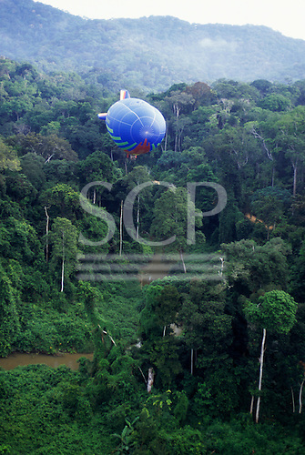Makande, Gabon. The Dirigible from the front flying over a river in the rainforest.