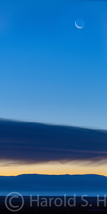A crescent moon rises in northern New Mexico near Taos.