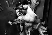 The San Francisco State Golden Gators baseball team celebrates with a festive dog pile in their locker room after clinching the 1995 NCAC Division title in San Francisco, California. (photo by Pico van Houtryve)