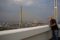 "Eli Evioni look out to the Chao Phraya river (and Rama 9 bridge) from the rooftop of their apartment building near Khao San Chabad in Bangkok, Thailand, on 13th December 2009. ..Eil: Aged 68; Born in Israel to parents from Yemen; grew up and joined the army, been through the wars of '56 and '67 where he first met people from Chabad who came to put tefillin and bring donuts even in the desert camps. Eli remembered seeing soldiers putting tefillin on tanks in '67 when 2 planes flew from the egyptian side. He thought that it was an attack but suddenly, the planes flipped, a sign of victory over the enemy. Left Israel to complete studies in England where he met his wife, Dina. Eli has worked in a musica theater for many years, and then became a jewellery designer, folowing family footsteps. After marriage, he travelled with Dina as spouse and stayed at home, building a house and bringing up the kids. Currently, Eli is writing a book about his life. They've been living in Bangkok for 5 years so far. Eli still feels the only home is Israel. ..Dina: Aged 66; Born in England to non-religious parents from East Europe, mostly Russia. Grew up very secular, ""felt like her birthright was stolen from her"". When she met Eli, he brought her back. but it was only when they moved to Thailand and was involved with Chabad that she really felt that Chabad was giving her heritage back. Dina worked and retired from the UN in Geneva. Now, she works as a freelance translator for the UN. ..They chose the flat because of its proximity to Chabad Khao San. They miss chabad khao san terribly whenever abroad. ""Once, I came back from a harsh time in Europe. I saw the face of the rabbi and his wife. their home was fully lit... and i felt like the light of G-d had entered me. I go to the synagogue every shabbat now.. like i never did before in my life. Because of Chabad. They give you love for free..."" says Eli...Photo by Suzanne Lee / For Chabad Lubavitch"