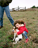 USA, California, girl embracing dog on a farm, Hwy 1 North of Bolinas