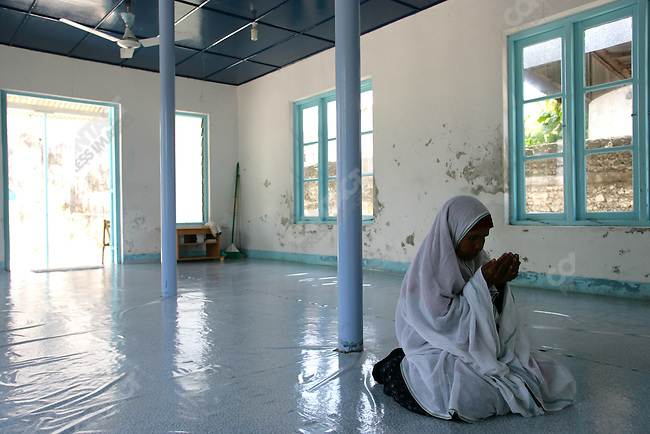 An elderly woman prays in a mosque reserved for women only.  Naalaafushi Island, The Maldives, April 2005.