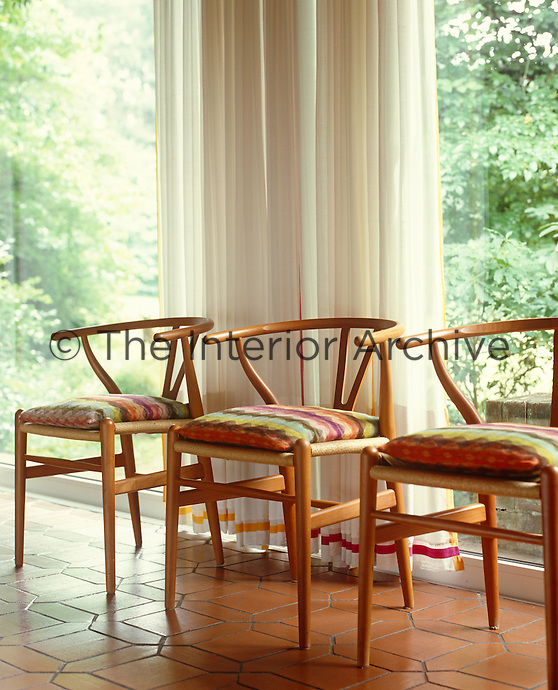Missoni fabric covers the cushions on three contemporary armchairs in the living room
