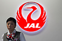 September 19, 2012, Tokyo, Japan - A Japan Airlines ground attendant stands in front of its logo at Tokyo's Haneda Airport on Wednesday, September 19, 2012...Once the national flag carrier, JAL was delisted after going bankrupt in 2010. It has since carried out cost cuts and restructured, returning to solid profitability. JAL shares rose about 2 percent on their return to the stock market  following a 663 billion yen ($8.5 billion) initial public offering that nearly doubled the money that went into the once-bankrupt carrier's bailout. (Photo by AFLO) UUK -mis-.