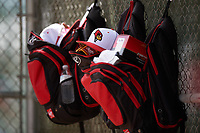Illinois State Redbirds backpacks hang from the dugout fence during a game against the Michigan State Spartans on March 8, 2016 at North Charlotte Regional Park in Port Charlotte, Florida.  Michigan State defeated Illinois State 15-0.  (Mike Janes/Four Seam Images)