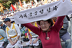 An older lady activist holds up a banner in Korean Hanggul at The National Worker`s Rally organised by Marxist groups and Doro Chiba labour union in Hibiya Park, Tokyo, Japan, Sunday, November 1st 2009
