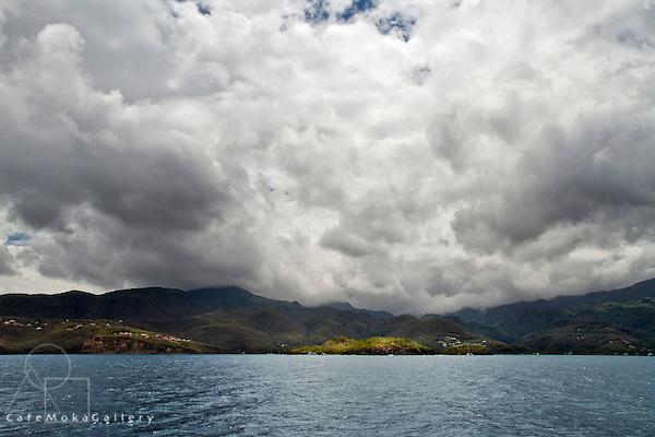 Pigeon Island illuminated bu sunlight with moody, cloudy sky
