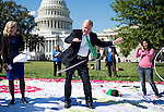 Sen. Tom Harkin, D-Iowa, hula hoops on top of a giant chutes and ladders game board on the east front of the Capitol during the National Women's Law Center and Mom's Rising event calling for pre-k education for all on Wednesday, Sept. 18, 2013. Chutes and Ladders was chosen as the ladders represent opportunities, and the chutes represent challenges families face finding affordable quality pre-k and childcare. (Photo By Bill Clark/CQ Roll Call)