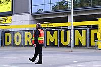 16th May 2020, Signal Iduna Park, Dortmund, Germany; Bundesliga football, Borussia Dortmund versus FC Schalke;  A steward with a mouth guard stands in front of the Signal Iduna Park in Dortmund