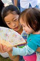 Hmong mom showing daughter the intricacies of a folding Hmong fan. Hmong Sports Festival McMurray Field St Paul Minnesota USA