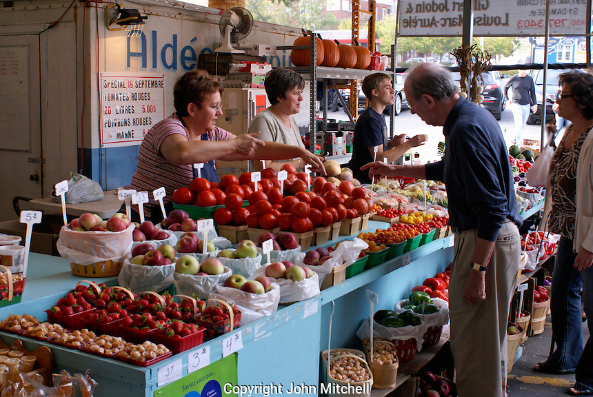 People shopping at a fruit and vegetable stand in the Atwater Market, Montreal, Quebec, Canada
