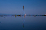 A lone drowned power pole is reflected in the still waters of the Salton Sea at the flooded marina in Bombay Beach, California
