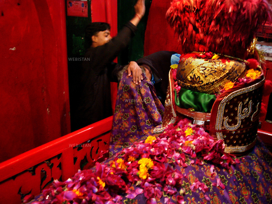 SEHWAN SHARIF, PAKISTAN - JANUARY, 2007:  A pilgrim visiting the shrine of one the disciples of Lal shahbaz Qalandar, a 13th century Sufi Master worshiped alike by Hindus and Muslims. Born as Seyed Shah Hussain (Usman) Marandi, he later on titled as Lal (red) Shahbaz ( Falcon) Qalandar (as he belonged to Qalandria order of sufism).