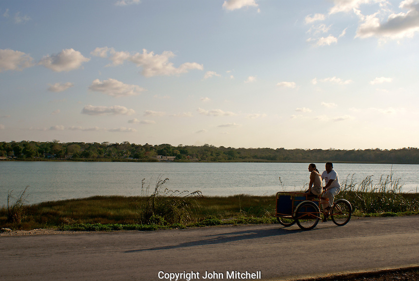 Couple riding a tricycle with Lake Coba in background, Coba, Quintana Roo, Mexico.