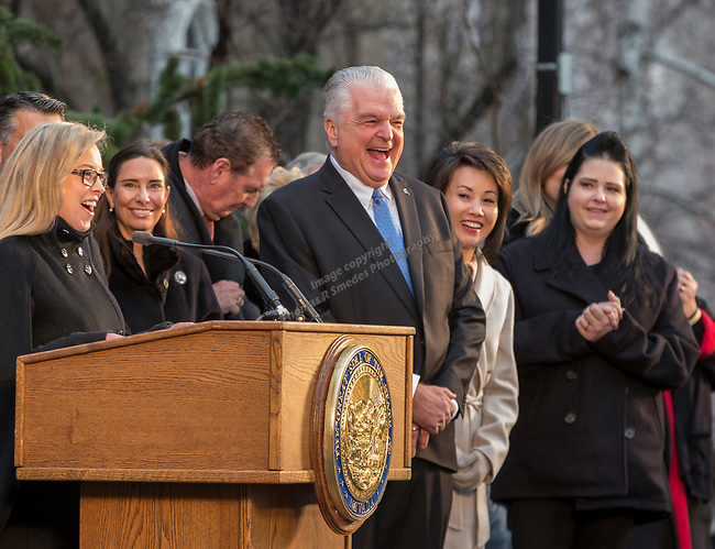 Governor-elect Steve Sisolak, center, laughs during his inauguration address on the steps of the Nevada State Capitol in Carson City, Nev., Monday, Jan. 7, 2019. (AP Photo/Tom R. Smedes)