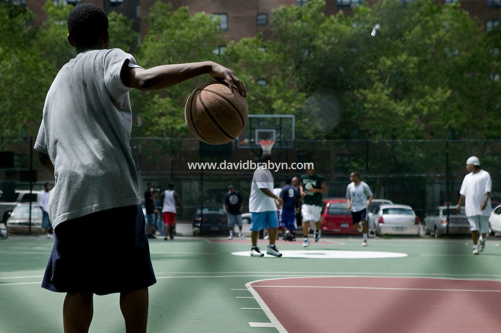 12 June 2006 - New York City, NY - A boy stands by the court to watch the tryouts for the Rucker's street basketball tournament at Rucker Park in Harlem, New York City, USA, Sunday June 12 2005. Photo Credit: David Brabyn