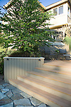 A sunny, summer scene of a raised, multi level residential deck constructed of Trex brand composite decking on a sloping lot in a suburb near Seattle, WA.