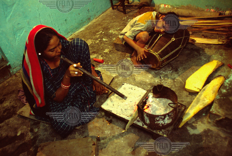 A young boy tunes his tabla, a North Indian drum, while his mother stokes the fire ready to cook the family's meal.
