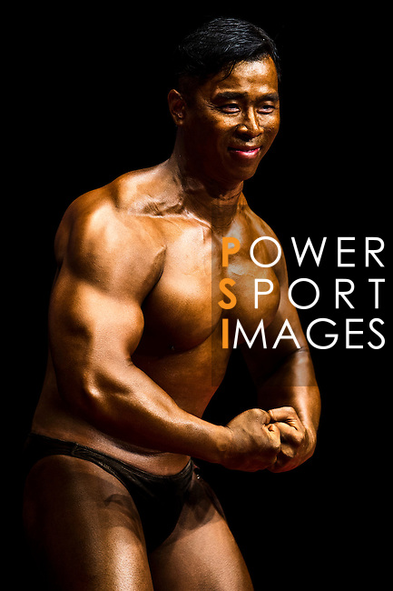 Chan Chi Ho flexes muscles for judges on stage during the Hong Kong Bodybuilding Championship on 29 June 2014 at the Queen Elizabeth Stadium Arena in Hong Kong, China. Photo by Aitor Alcalde /  Power Sport Images