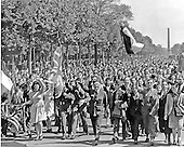 Paris, France - May 8, 1945 -- Joyous Parisians and Allied soldiers tramp through the Champs Elysees, a well known thoroughfare in Paris, France on May 8, 1945, celebrating Victory in Europe (V-E) Day..Credit: U.S. Army via CNP