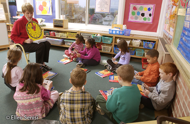 MR / Schenectady, NY.Yates Arts-in-Education Magnet School (urban school) .First grade / Second grade multi-level classroom.First grade students set hands on small play clocks during math lesson with teacher on telling time. .MR: L-C.©Ellen B. Senisi