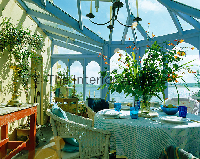A round table and wicker chairs take centre stage in this light-filled conservatory which has views across a lake
