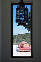A Moroccan lantern in the stairwell echoes the colourful geometric pattern of the cushions on the terrace