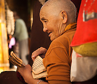 Buddhist nun reading sacred scriptures in front of Jokhang temple
