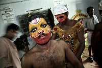A Thayam artist is being prepared before his performance, Thirupunithura, Ernakulam, Kerala, India