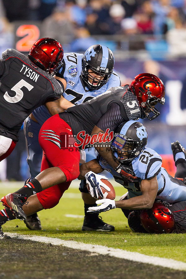 Romar Morris (21) of the North Carolina Tar Heels is hit by Adrian Witty (8) and Greg Blair (51) of the Cincinnati Bearcats during the Belk Bowl at Bank of America Stadium on December 28, 2013 in Charlotte, North Carolina.  The Tar Heels defeated the Bearcats 39-17.   (Brian Westerholt/Sports On Film)