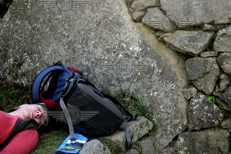 A woman rests on one of the grass terraces of Machu Picchu, the so called 'Lost City of the Incas'.