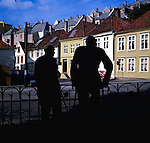 Two elderly men one with walking sticks silhouetted against a row of wooden fronted houses in Bergen, Norway.