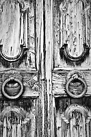 Detail of a door and its knobs and rings of an old house in villa saletta, toscany, italy. Black & white