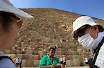 A Foreign tourists is seen putting a face mask as they visit the Pyramids in the Egyptian capital of Cairo on June 16, 2009. Egypt, hard hit by the more deadly H5N1 bird flu virus, detected its first H1N1 case early this month in a 12-year-old American girl who arrived for a holiday in the most populous Arab country. To date, 18 cases of H1N1, formerly known as swine flu, have been reported in the country. Photo by Wissam Nassar.