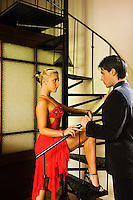 Argentina, Buenos Aires, Tango dancers standing by spiral staircase