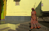 Mumbai, Banganga area women walking past a small Hindu temple