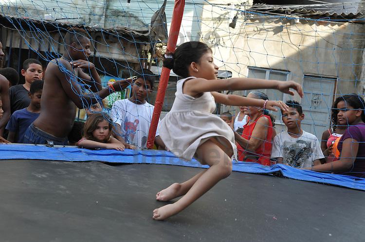 Menina brinca no pula pula, na comunidade do Parque Everest. Conjunto de favelas do Alemão, Rio de Janeiro, Brasil.