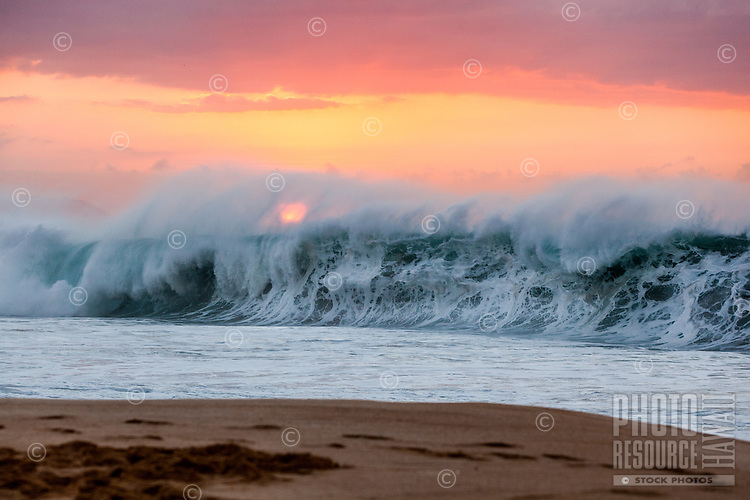 A powerful wave breaks under an orange sunset at Ke Iki Beach, North Shore, O'ahu.