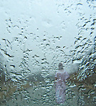 A woman walks down the road as she's viewed through a rainy windshield.