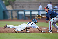 Robert Javier (33) of the Pulaski Yankees dives back towards first base as Bryce Ball (19) of the Danville Braves waits for a pick-off throw at Calfee Park on June 30, 2019 in Pulaski, Virginia. The Braves defeated the Yankees 8-5 in 10 innings.  (Brian Westerholt/Four Seam Images)