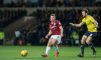 Lawson D'Ath of Northampton Town plays a pass under pressure from Jake Wright of Oxford United during the Sky Bet League 2 match between Oxford United and Northampton Town at the Kassam Stadium, Oxford, England on 16 February 2016. Photo by Andy Rowland.