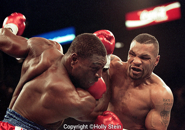 Mike Tyson throws a right at Frank Bruno during their heavyweight championship fight.  Tyson won by TKO in the 3rd round to win the WBC heavyweight title.