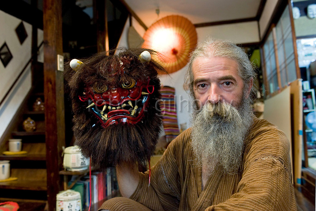 Briton Jake Davies poses for a photo with one of his Iwami-Kagura masks -- the Akaoni (red demon) from Iwami-Kagura dance --  at his home in Sakurae Village, Shimane Prefecture, Japan on 28 June 2011..Photographer: Robert Gilhooly