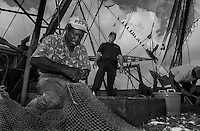 An officer with the United States Coast Guard looks on as Gene Orage makes repairs to the Turtle Extruder Device (TED) on his shrimp net. TED's are required so that sea turtles that get caught in the nets can escape. Many shrimpers complain that the device also lets out the shrimp.