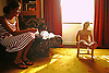 Mother and young son backlit from sunny window and a victorian sofa with a drop down end.<br />
