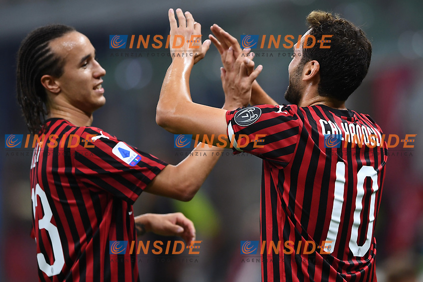 Hakan Calhanoglu of AC Milan (R) celebrates with Diego Laxalt after scoring the goal of 1-0 during the Serie A football match between AC Milan and Atalanta BC at stadio Giuseppe Meazza in Milano ( Italy ), July 24th, 2020. Play resumes behind closed doors following the outbreak of the coronavirus disease. <br /> Photo Image Sport / Insidefoto