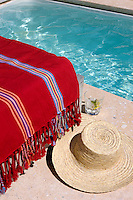 A straw hat and striped throw on the stone floor of the terrace that surrounds the outdoor swimming pool