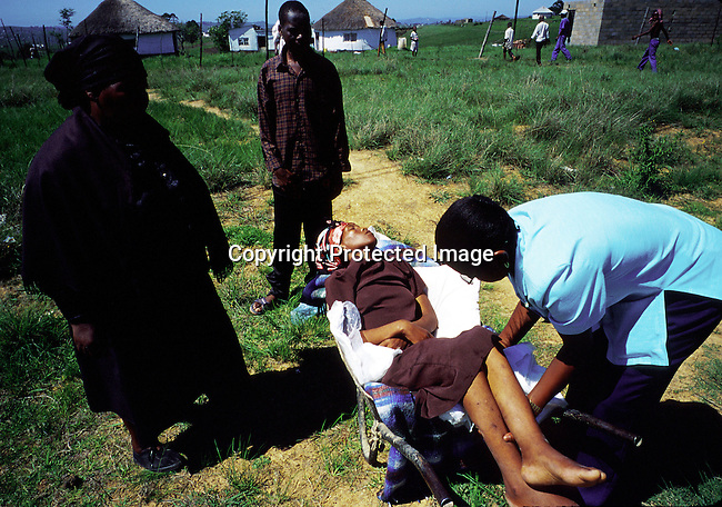 Busisiwe Mfeka, age 28, is dying of Aids, and coming home on November 22, 1999 to her village in Izingolweni in Southern Natal South Africa with her mother (left). She was taken in a whellbarrow by her brother (center) to the family house. Se died the following day. .(Photo Per-Anders Pettersson/ Liaison Agency)