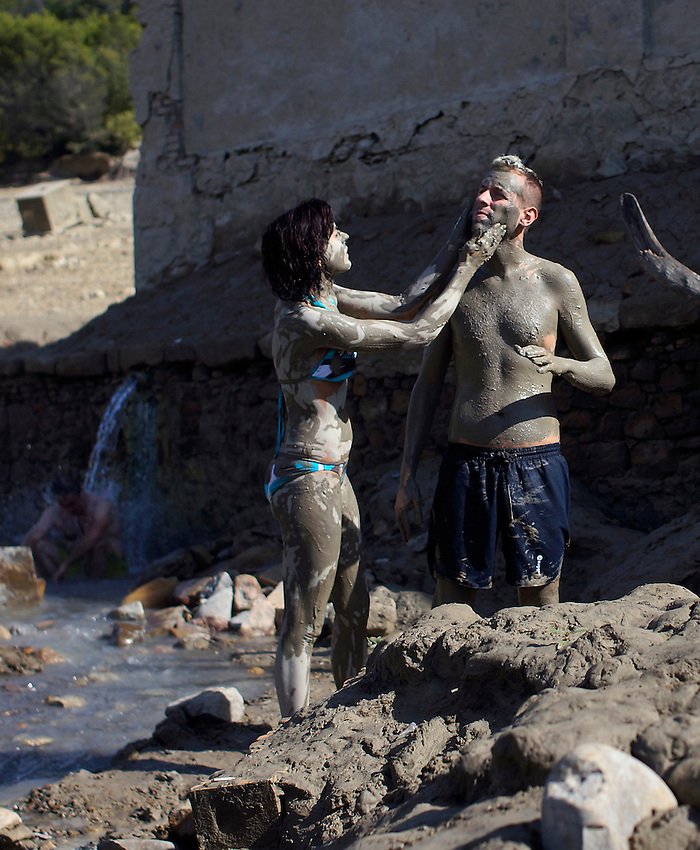 A couple covered in mud repose in the ancient Baths of sulphurous waters of Tiermas on October 13, 2012, in the Spanish reservoir of Yesa. The ancient baths of sulphurous waters of Tiermas are under Yesa reservoir waters and return to the surface when the reservoir is running low on water.  Photo: Ander Gillenea